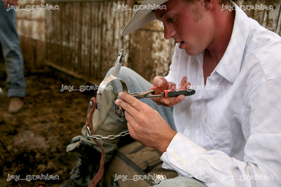 Tyler Adrian, Marshall, MO, repairs one of his spurs before the start of the National Federation of Professional Bullriders competition at the Coles County Fair ground in Charleston, Illinois on Saturday, August 1, 2009.  (Jay Grabiec)