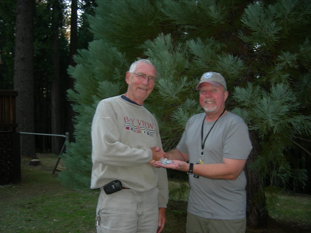 Bob Pelikan receives his 15-year, 20-year and 25-year membership pins from VP Peter Oxenbol.