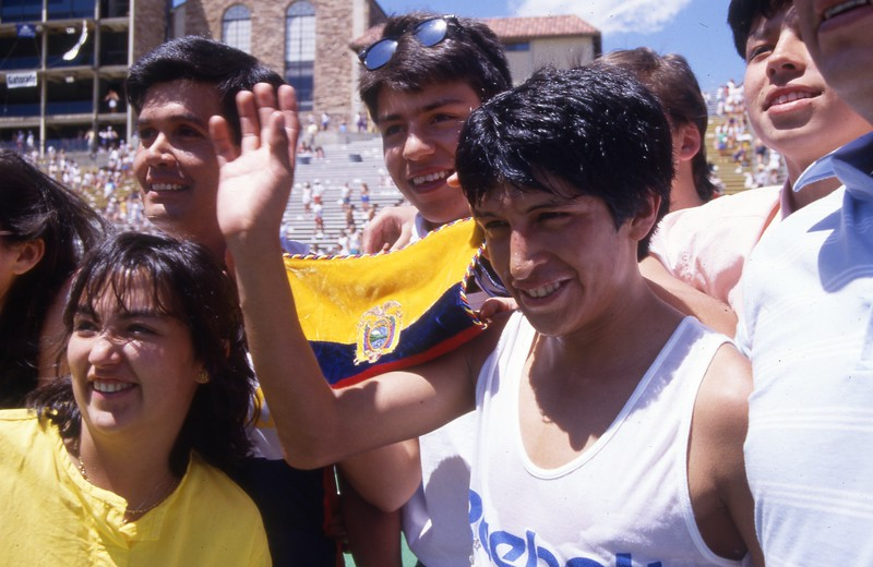 1988 Bolder Boulder winner Rolando Vera is mobbed in Folsom Field and draped with the flag from Ecuador.