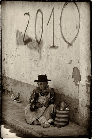 A local Bolivian lady gets some respite from the busy Tarabuco market.  2011 (The graffiti was so passé).