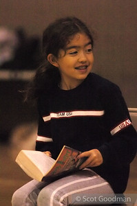 "Aya (Jonathan's daughter) reads ""Harry Potter"" on the sidelines."