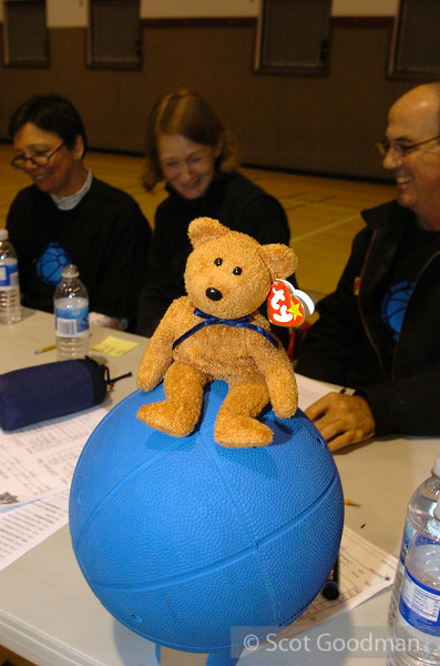 Volunteer beanie baby bear sitting atop a goalball at the score table. Scorekeepers keep track of time allowed to hold the ball, number of throws in a row per player, and other rules. A scorekeeper will launch this happy little fellow onto to the court to alert the referee to stop play if he or she spots an infraction.