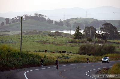 6:35 am Sunday morning, Lake Herman Road, Benicia/Vallejo. Mile 251. 20.5 hours, 203 miles have elapsed since my last photo. I caught up with Lee the next morning, Sunday, near Lake Herman (seen in the background). Lee (second from left) has been on his bike for nearly 25 hours. Lee's friends, Micah, Tommy, and Brent, joined Lee the previous evening to keep him company through a long night through the Sonoma and Napa hills, driving a sag car, as well as riding with him in the cold.