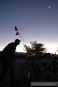 Greg prepares bikes under a predawn sky and rising almost new moon.