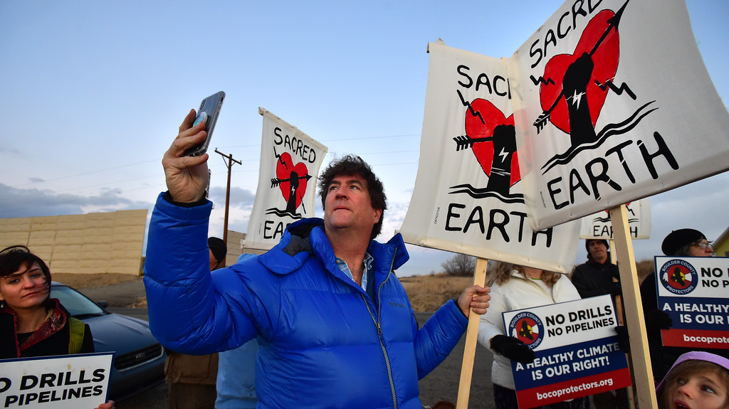 . Thomas Williams takes photos as the Boulder County Protectors protest against a well in Weld County on Friday.  For more photos and video go to dailycamera.com. Paul Aiken Staff Photographer December 12 2017.
