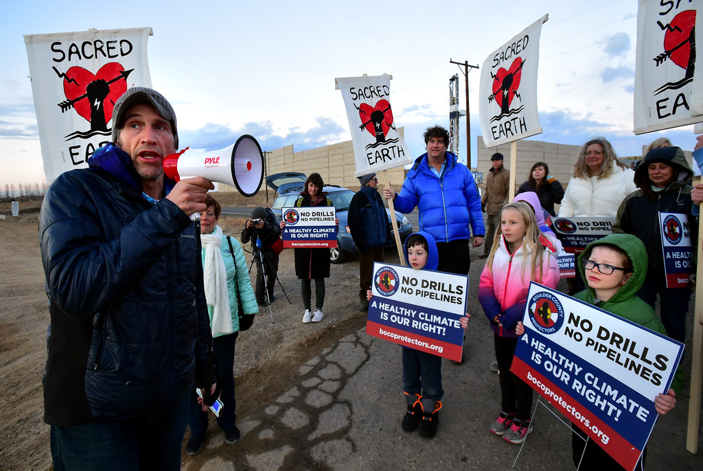 . David Paul speaks to the assembled protestors as the Boulder County Protectors protest against a well in Weld County on Friday. A couple of young protestors listen in from left to right, Charlie Willmeng, Siena Scornavacco and Gabriel Stets For more photos and video go to dailycamera.com. Paul Aiken Staff Photographer December 12 2017.