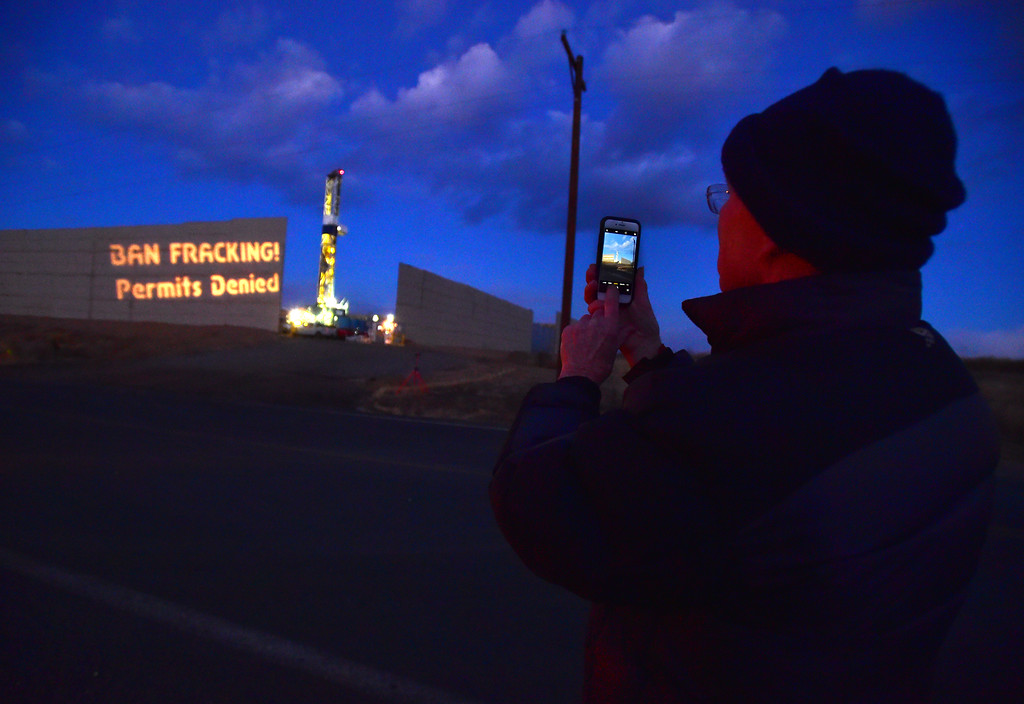 . John Lamb takes a photo of a projected slogan on a sound wall as the Boulder County Protectors protest against a well in Weld County on Friday.  For more photos and video go to dailycamera.com. Paul Aiken Staff Photographer December 12 2017.