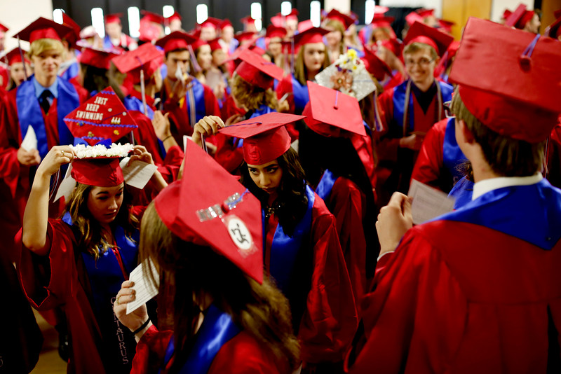 Students from the 2016 graduating class from Centaurus High School make last minute adjustments to their caps and gowns before their entrance to the arena May 21 at the Coors Events Center. <br /> Photo by Philip B. Poston