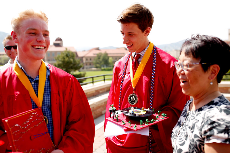 Justin Krawetz, left, and Jack Spice, center, show their mortar board designs to Louise Garrels, of Lafayette, before the Centaurus Class of 2016 Graduation, May 21 at the Coors Events Center. Krawetz took humor in the fact that what was supposed to represent mountains on his mortar board, wasn't exactly clear. <br /> Photo by Philip Poston