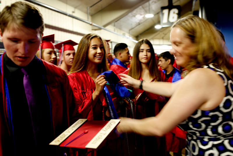 Maddie Chism, center left, receives her stole from Lisa Lowe prior to the 2016 commencement for Centaurus High School, May 21 at the Coors Events Center.<br /> Photo by Philip B. Poston