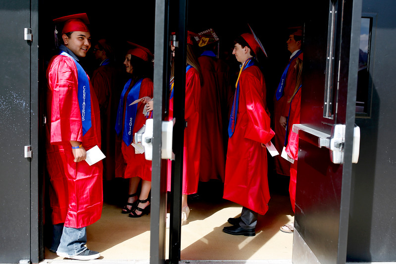 Patiently waiting to enter the arena before the commencement ceremony, Isaac Rodriguez pokes his head out for some fresh air, May 21 at the Coors Events Center. <br /> Photo by Philip B. Poston
