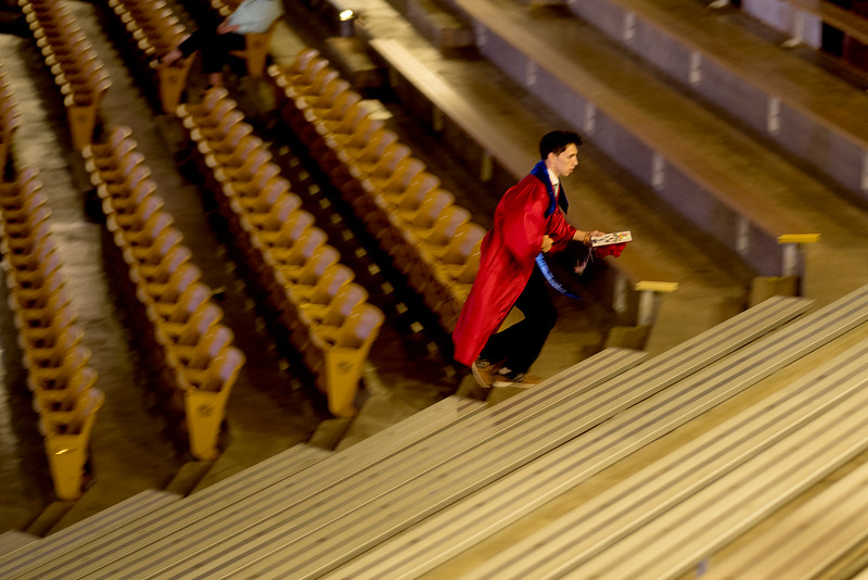 Not wanting to be late for Centaurus High School pre-graduation staging, Hendrix Taylor hustles up the arena stairs May 21 at the Coors Events Center. <br /> Photo by Philip B. Poston