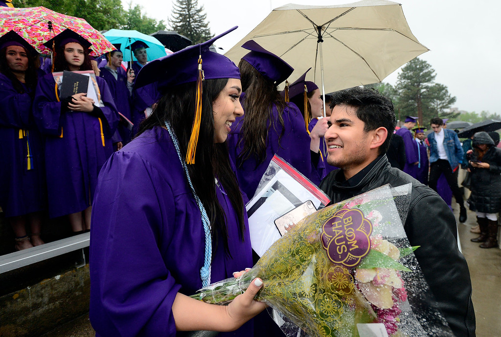 . Adela Aguirre gets flowers from her boyfriend Jesus Eduardo at the Boulder High School Commencement on Recht Field on Saturday. For more photos go to dailycamera.com. Paul Aiken Staff Photographer