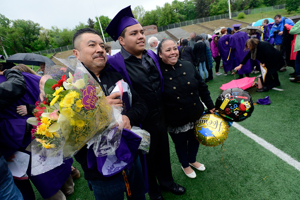 . Dad Arturo Alvarez and mom Guadalupe Martinez get a proud photo taken with their son Andres Alvarez Martinez at the end of the Boulder High School Commencement on Recht Field on Saturday. For more photos go to dailycamera.com. Paul Aiken Staff Photographer