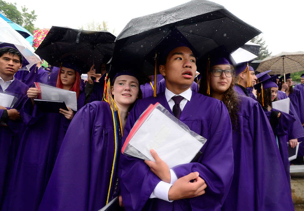 . From left to right, Cassidy Adams, Dean Abraham and Christine Abdel huddle under an umbrella during the chilly and wet  Boulder High School Commencement on Recht Field on Saturday. For more photos go to dailycamera.com. Paul Aiken Staff Photographer