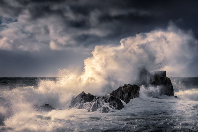 Huge waves covering the beacon at the Cape on Bowen just as some sunlight hit the wave.