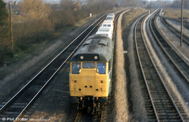 A class 31 with motor vehicles passes Hinksey at speed in 1979.
