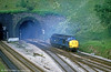 A class 37 leaves a trail of exhaust fumes as it leaves Hillfield Tunnel, Newport in July 1985.