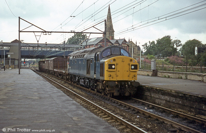 The spire of St. Stephen's Church, Audenshaw provides a backdrop to 40136 heading a freight through Guide Bridge on 18th August 1980.