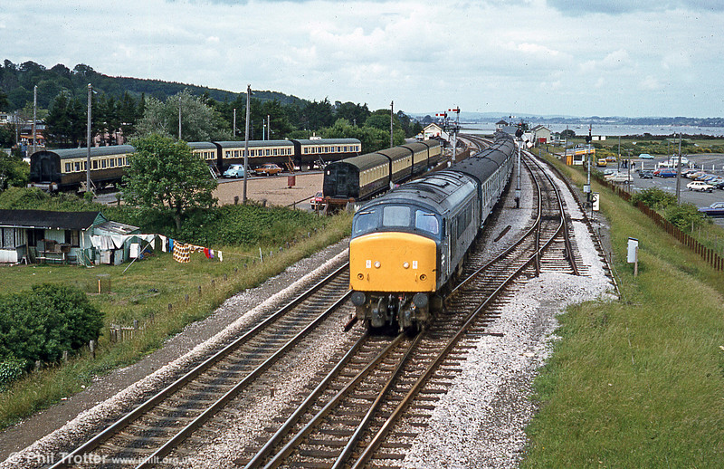 The camping coaches at Dawlish Warren make an interesting backdrop to this view, taken c.1980. A Camping coach was first stationed in the goods yard in 1935, for rental by holidaymakers but the facility was withdrawn in 1940. Camping coaches were reintroduced in 1952, and by 1959 there were nine coaches stationed here as above. After 1964 the public camp coach service was withdrawn but the coaches at Dawlish Warren continued to be managed by the British Rail Staff Association for its members. The old coaches were replaced for the 1982 season by BR Mk1s, since when the connection to the goods yard has been removed.
