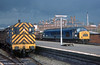46001 waits for the road with a freight, while a class 08 passes on a trip working under stormy skies at Shrewsbury on 18th September 1975.