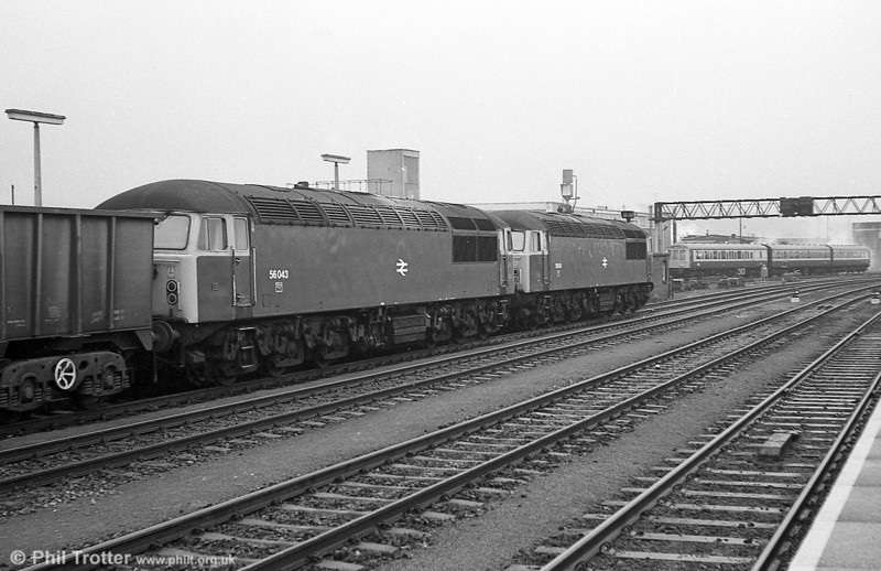 A pair of class 56s with 56043 as train engine at the head of one of the legendary ore trains at Cardiff Central. A suburban dmu on a Valley Lines service leaves a smokescreen in the background.