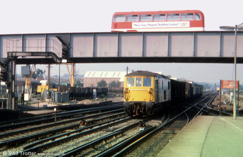 A class 73 hauled freight passes beneath a Hants & Dorset Bristol FLF at Eastleigh on 29th August 1975.