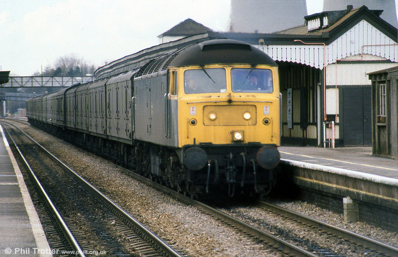 An unidentified class 47 speeds through Didcot with newspaper empties, April 1985. Loco unknown.