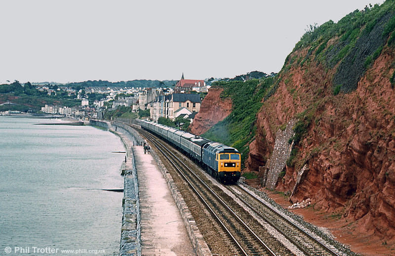 On a perfectly calm day in the mid 'eighties, a northbound express accelerates away from Dawlish. The length of trains in those days, compared with the Cross Country four or five car units of today, is obvious. Loco unknown.