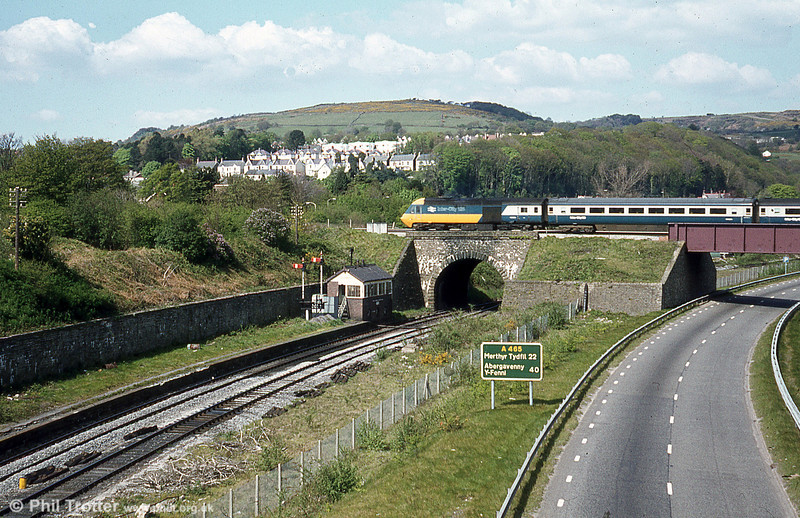 A Paddington to Swansea HST crosses over the Vale of Neath line in the early 1980s. The clear view of the former Neath Riverside Station and signal box is no longer possible due to the growth of vegetation.