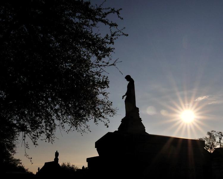The sun rising behind an angel.