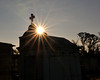The sun peeking further over a tomb in New Orleans.