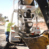 Oct. 29, 2010: A back hoe is pressed into service as a concrete bucket.  A culvert is being created to carry runoff from the pond to storm drains.