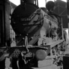 """Q class, 30530, in the lifting shed at Bournemouth MPD on 16 August 1955.  Note the """"smiley face"""" that some humourist has chalked on the buffer!"""