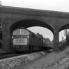 "This shot is included in a number of ""Newbury Race Special"" photos, but it looks like a scheduled West Country service to me.  An unidentified Western Class 52 passes under Bath Road Bridge, Reading in 1962."