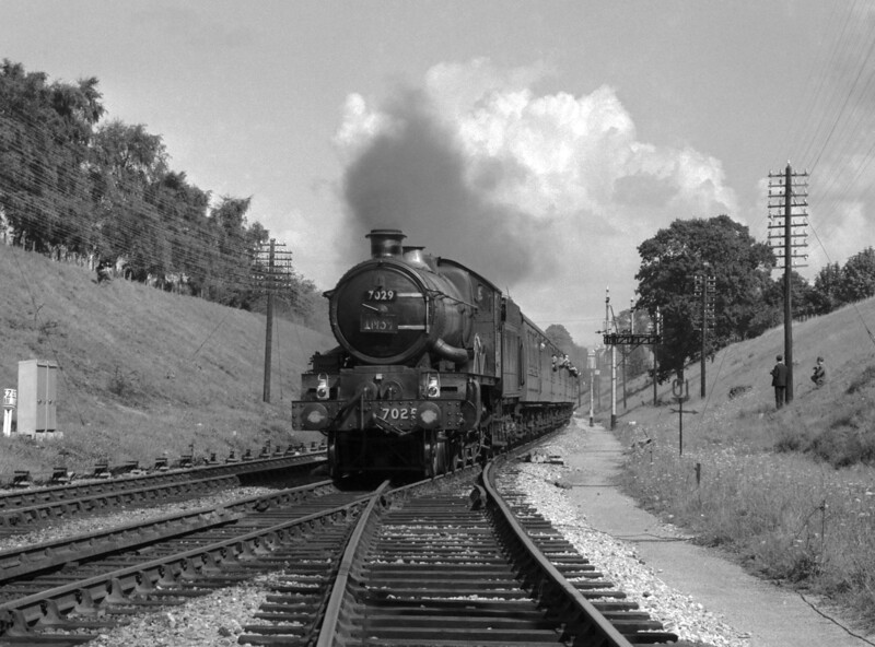 "Another of the ""sundry loose negatives"", but one that holds some points of interest.  7029 Clun Castle heads a train of enthusiasts (?) past Southcote Junction.  The date is uncertain.  However, 7029 was withdrawn from service in December 1965 and was noted by the ""Railway Observer"" as working the last steam roster on 1M39 from Penzance to Wolverhampton on 4 September 1965 (by special request of the Cheltenham branch of the RCTS).  In this shot, 7029 still carries the 1M39 head-code.  Also of note is that the triple bracket is now devoid of its signal arms and colour light signalling is in place."