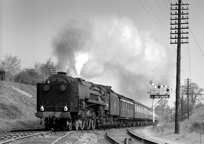 "71000 Duke of Gloucester passes Southcote on trial with the dynamometer car behind.  This is taken from a glass quarterplate and is a little grainy.  However, there weren't many chances to photograph the ""Duke"" at Southcote.  The record says 23 April 1955, which would be very soon after the new bracket signal shown had been installed.  Note the railway employee standing behind the screen on the front of the locomotive!"