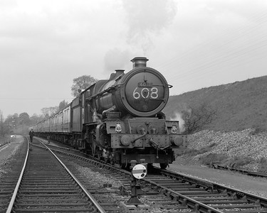 Here we have another shot of a King on a West Country bound express at Southcote.  Although the train reporting number suggests that this is an up train from Penzance to Paddington, the train is clearly headed toward Penzance!  The date is uncertain although it must be after 6017 King Edward IV received a double chimney in December 1955 and it is likely sometime in 1956.  For some reason the train has been brought to a halt and it looks as though the guard might be on his way to ascertain the cause from the signal box!