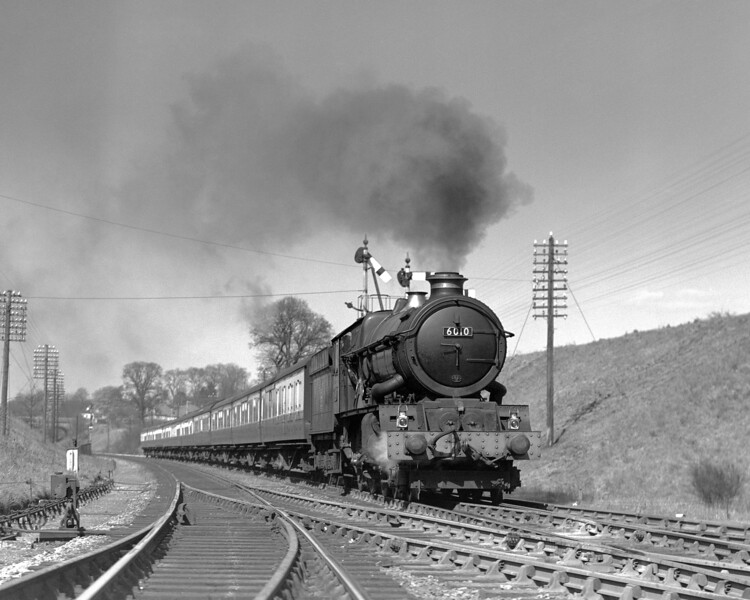 """This is one of many shots of the 1.30pm ex-Paddington at Southcote.  On this occasion 6010 King Charles I heads a train of just pre-Mk1 stock on 16 April 1955.  The picture was taken on the far from mobile Adams plate camera and my father seems to be standing in the up main whilst the Oxford Road starter in the background is clearly """"off""""."""