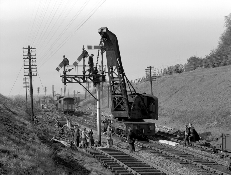 Another shot of the relaying works at Southcote on 26 May 1956.  Here the team is giving attention to the bracket signal which had itself only been installed a little over a year earlier.  Perhaps it was necessary to move it a little further towards Reading West to accommodate the new junction?  Any information on this would be gratefully received.  Of particular note to me is the vast number of bicycles in evidence both round near the signal and down by the signal box.  Clearly all the workmen arrived on site by bike.