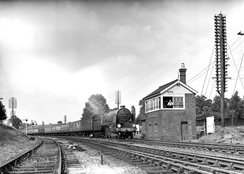 30738 King Pellinore heads the down York to Bournemouth past Southcote Junction signal box in the early 1950s.  Signalman Sweetzer is leaning out of the window.  I have included this shot because it is perhaps the best surviving view of the signal box itself despite a rather unusual lighting effect across the locomotive.  Looking at the plate closely, it looks as though some steam has been left hanging in the air.