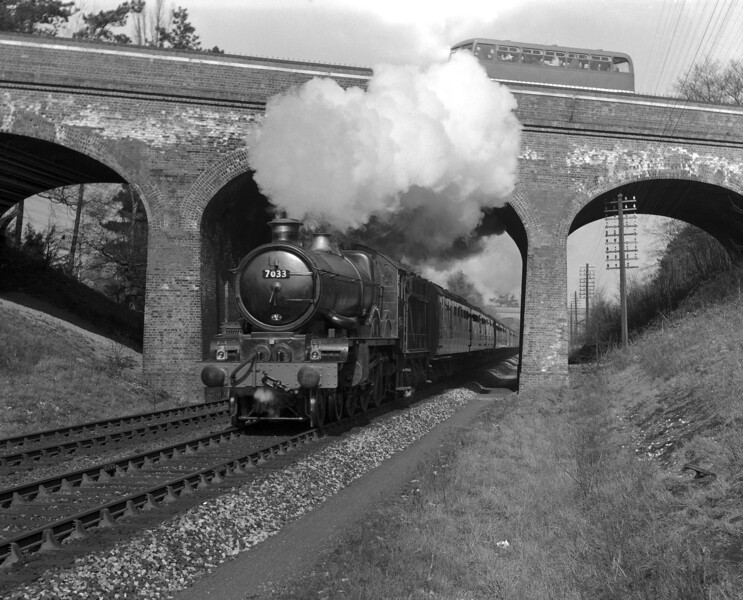 7033 Hartlebury Castle passes under the Bath Road bridge approaching Southcote with a Newbury race meeting special in the late 1950s.
