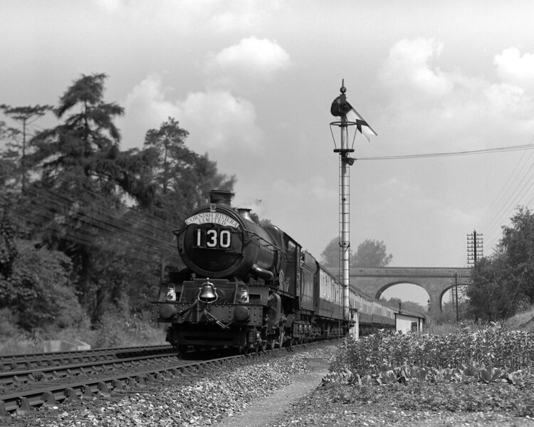 6000 King George V on the down Cornish Riviera photographed between the Tilehurst and Bath Road bridges on the approach to Southcote.   This spot was the setting for some of M W Earley's most iconic pictures of the King class.  This photograph was taken in 1956 shortly after the new style of train headboard came into use.