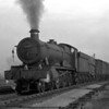 There are very few photographs of goods trains in the portfolio.  Here Hall class 4987 Brockley Hall is seen moving off the Oxford Road triangle towards Tilehurst at Reading West Junction in the weak winter sunlight of 1957-58.
