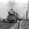 "From its inception, The Royal Duchy was a favourite subject.  Here an unidentified King heads the train round the ""fairground"" curve from Reading West Main to Reading West on 12 October 1957."