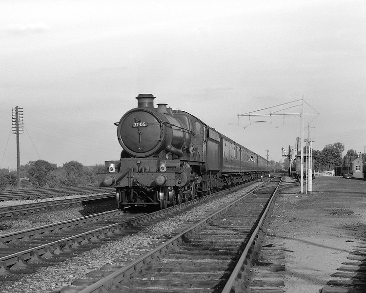 "Castle Class 7005 heads a down express approaching Tilehurst.  It appears that this picture was taken in 1957 and the absence of the designation ""Castle Class"" below the name of the locomotive indicates that 7005 was still named Lamphey Castle:  renaming to Sir Edward Elgar took place in August 1957.  Who knows what the passenger leaning out of the second carriage window was thinking of?"