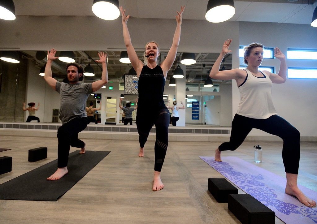 . Instructor Tamara Burke, center, works with Shaun Kremin left, and McKenna Rohner during the Bulldog Yoga\'s Invigorate class in Boulder on Monday March 5. For more photos go to dailycamera.com. Paul Aiken Staff Photographer March 5 2018