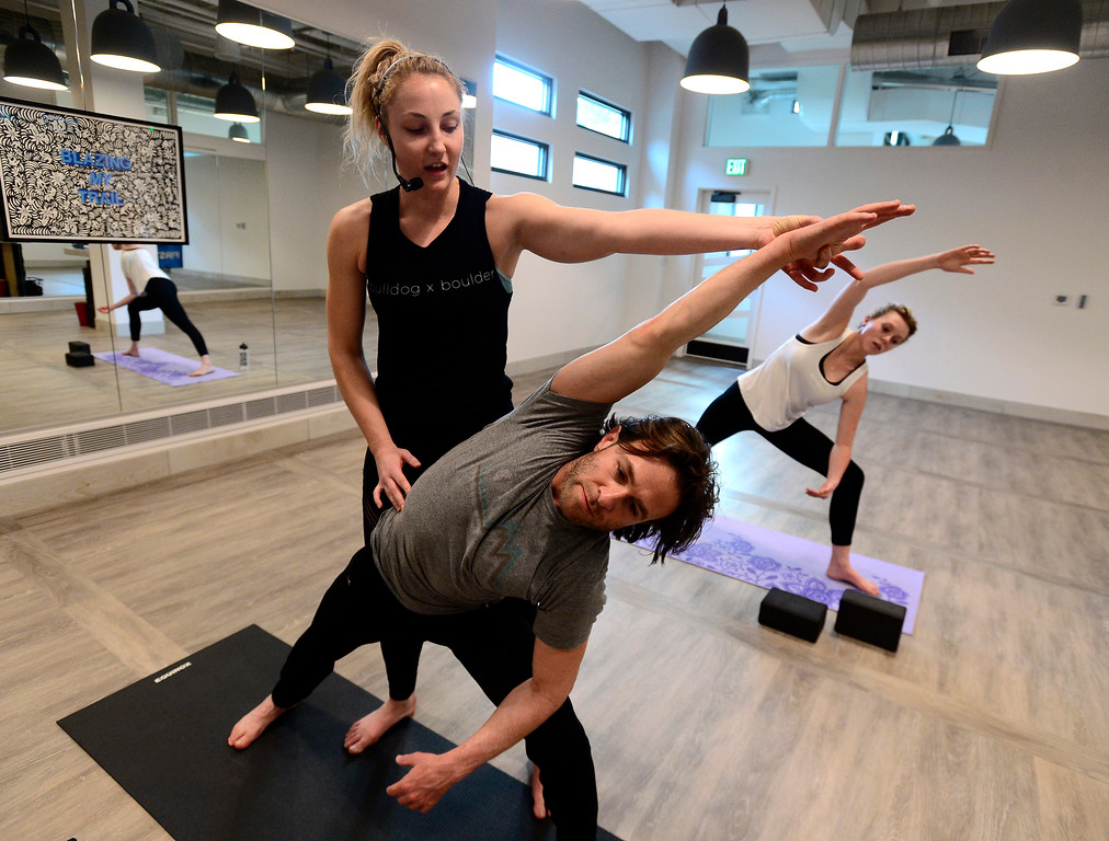 . Instructor Tamara Burke checks Shaun Kremin\'s form during the Bulldog Yoga\'s Invigorate class in Boulder on Monday March 5. For more photos go to dailycamera.com. Paul Aiken Staff Photographer March 5 2018