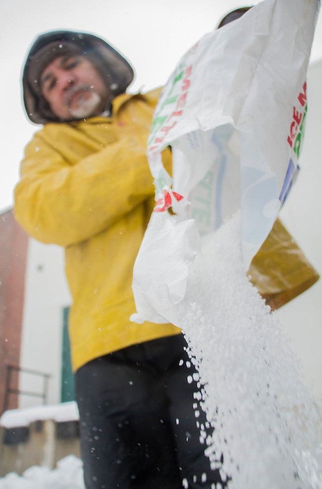 February  5, 2014 -- Valdir Dossontos  pours rock salt into a bucket to use on a sidewalk along Commonwealth Ave. in Allston, Mass. Photo: Carolyn Bick/BU News Service.