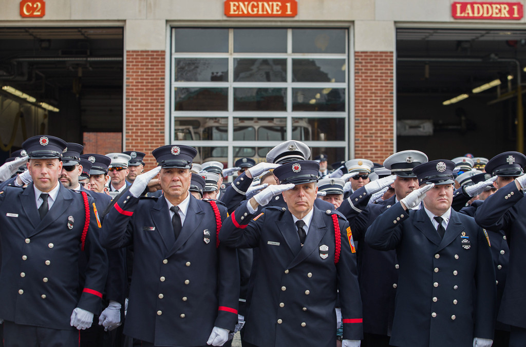 April 2, 2014 - Firefighters from the Boston and Watertown fire departments stand at attention outside of the firehouse in Watertown, Mass., as the hearse carrying Lt. Edward Walsh Jr. proceeded past en route to St. Patrick's church. Lt. Walsh was killed on duty while responding to a fire on Beacon St. in Boston, Mass., on March 26, 2014. Photo by Taylor Hartz/Bu News Service.